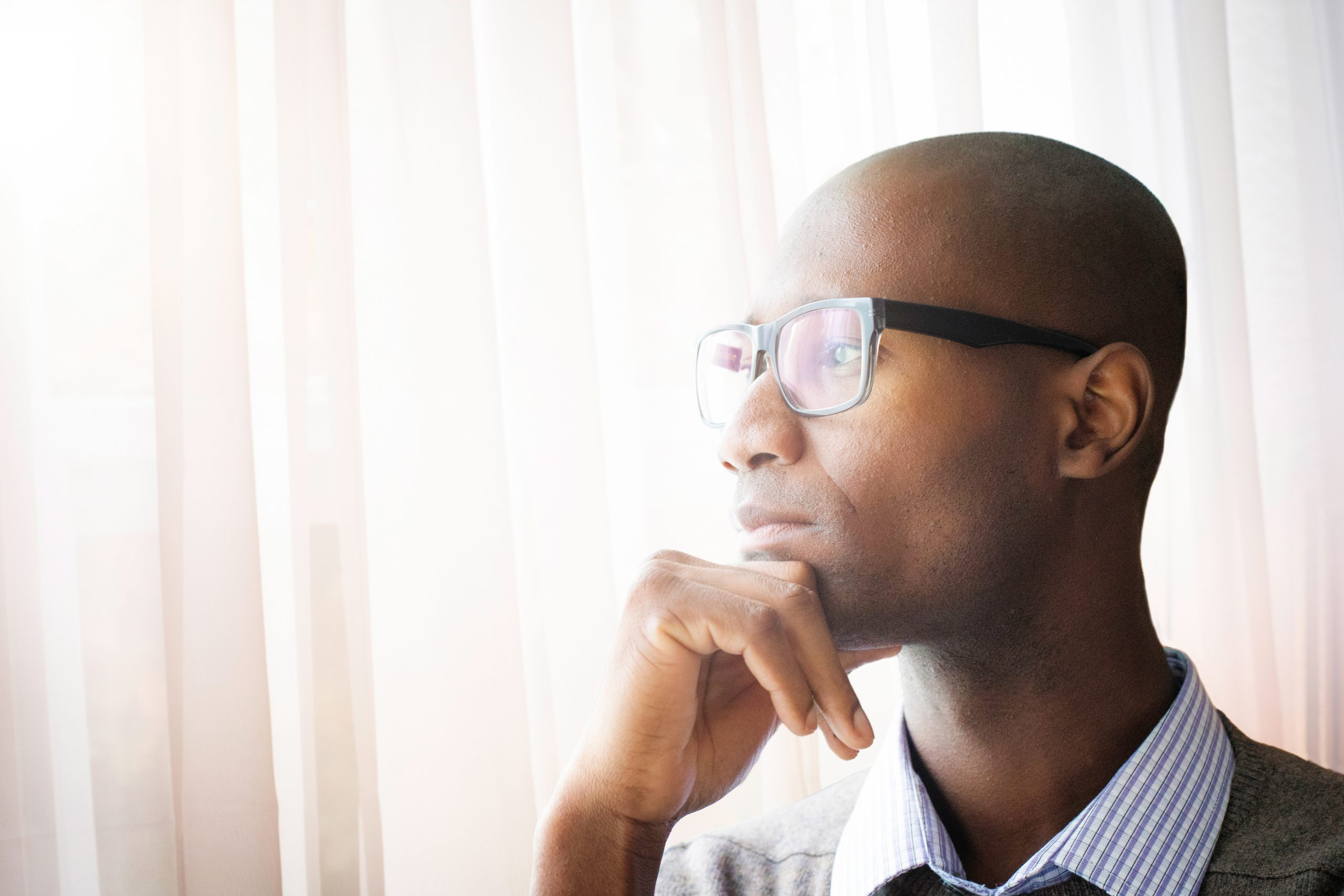 Pensive mature bald black man by a window resting his chin on his hand. He is wearing glasses, a shirt and a sweater.