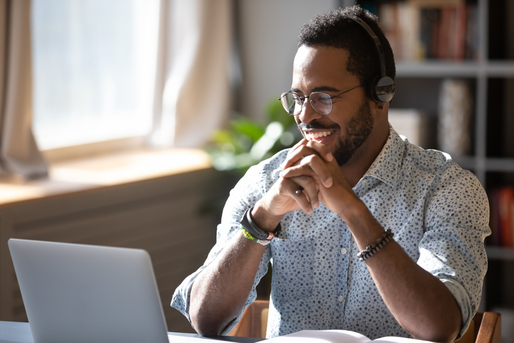 Happy millennial african american man in glasses wearing headphones, enjoying watching educational webinar on laptop. Smiling young mixed race businessman holding video call with clients partners.